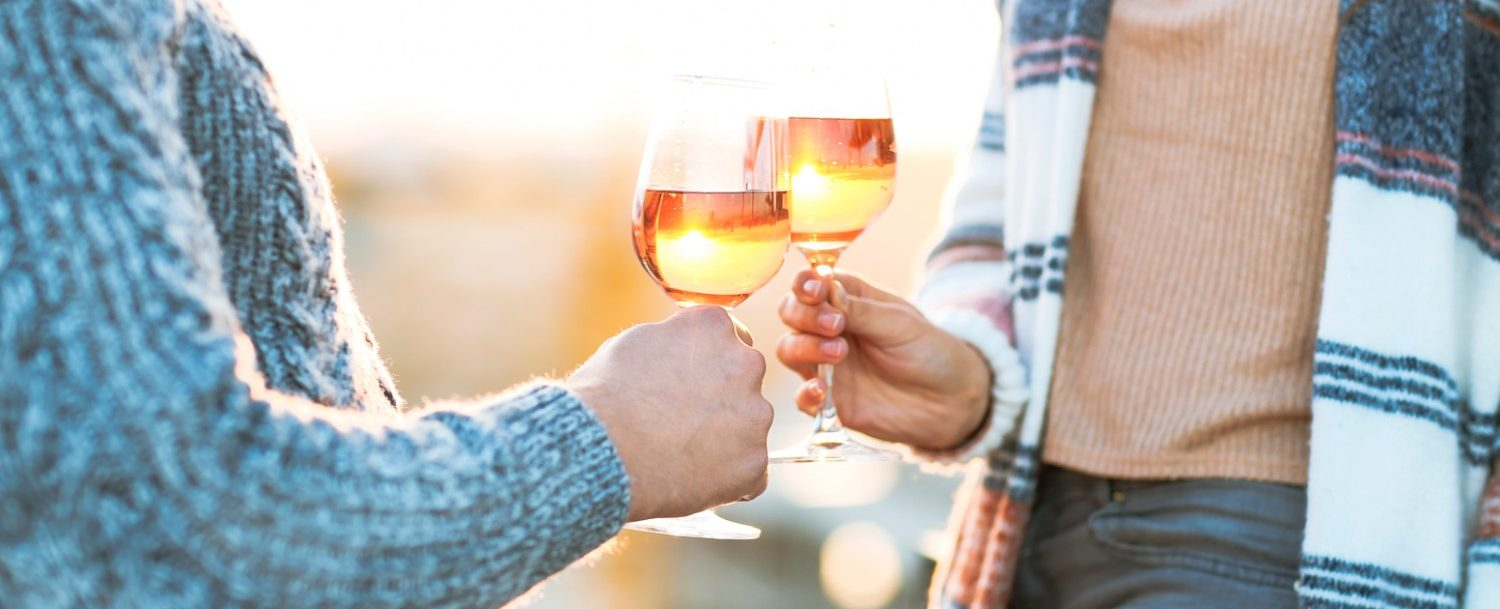 Man and woman with glass of rose wine at a fall festival